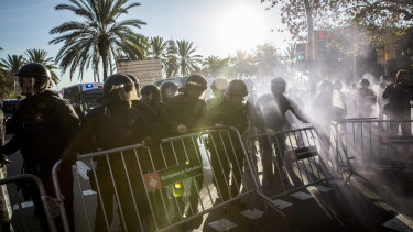 Riot police remove a barrier during a protest by supporters of Catalan independence on Paralelo Avenue in Barcelona, Spain.