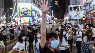 A demonstrator raises his hand as he blocks traffic on Hennessy Road during a protest in the Causeway Bay district of Hong Kong.