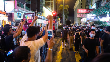 Pedestrian cheer as demonstrators march on Nathan Road during a protest in the Mong Kok district of Hong Kong, on Sunday.