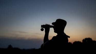 A member of the Lithuania State Border Guard Service looks through binoculars as he patrols on the border with Belarus, near the village of Purvenai, Lithuania.
