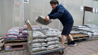 A customer loads sand bags at a hardware store in Kanagawa Prefecture.