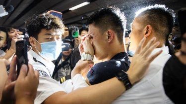 A man alleged to be a mainland police officer, centre, is surrounded by security officials and protesters at Hong Kong International Airport.