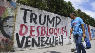 A pedestrian in Caracas passes graffiti protesting against US President Donald Trump's sanctions on Venezuela.