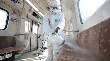 Workers wearing protective suits spray disinfectant inside a subway  in Seoul, South Korea.