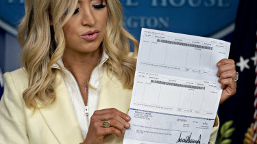 Kayleigh McEnany, White House press secretary, holds a cheque in the amount of US President Donald Trump's annual quarterly salary, to be donated to the US Department of Health and Human Services.