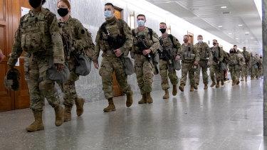 Members of the National Guard walk through Dirksen Senate Office Building in Washington, DC