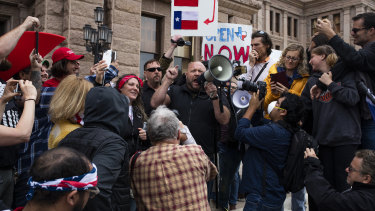 Alex Jones, radio host and creator of the website InfoWars, speaks into a megaphone as demonstrators gather outside the Texas State Capitol.