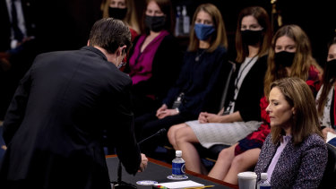 Supreme Court nominee Amy Coney Barrett watches as an aide tests her microphone during a confirmation hearing before the Senate Judiciary Committee.