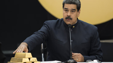 Venezuelan President Nicolas Maduro touches gold bars at a press conference  in Caracas in 2018.