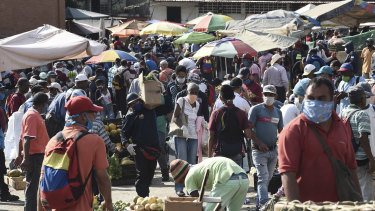 Shoppers wearing protective masks walk through the crowded Coche market in Caracas, Venezuela.