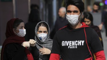 Pedestrians wear masks to help guard against the Coronavirus, in downtown Tehran, Iran.