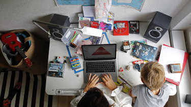 A woman works at a desk in a bedroom as a child sits nearby in Bern, Switzerland.