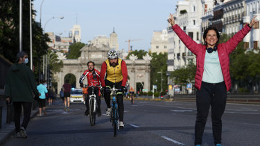 Working from home also means time to get out of the house for exercise: people running and cycling through Madrid's Puerta de Alcala.