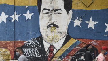 Pedestrians wearing protective masks walk by a mural of President Nicolas Maduro in Caracas, Venezuela, on Tuesday.