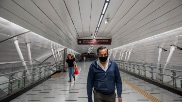 People wearing protective masks walk through the Plaza de Armas subway station in Santiago, Chile.
