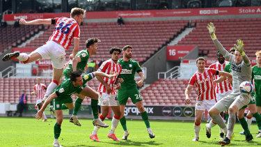 Harry Souttar heads the ball wide past Daniel Iversen of Preston North End.
