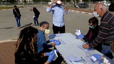 An inconclusive election: Israelis wore protective face masks to cast their votes at a special polling station set up for people quarantined for potential exposure to coronavirus in Ashkelon, Israel on March 2.