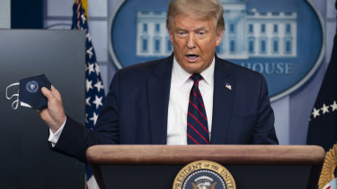 President Donald Trump holds a mask as he speaks during a news conference at the White House.