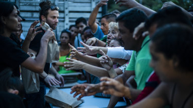 World Central Kitchen volunteers, left, distribute food in Cucuta, Colombia.
