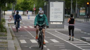 A cyclist wearing a face mask rides past a jogger in a cycle lane in Madrid, Spain.