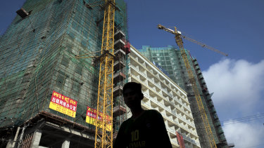 A pedestrian walks past a construction site in Sihanoukville, Cambodia as yet another Chinese-funded building goes up.