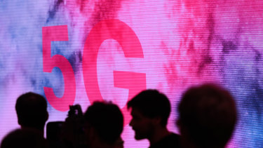Attendees are silhouetted beside a 5G display on the Deutsche Telekom exhibit in Berlin.