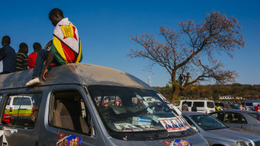 A supporter wearing a Zimbabwean national flag while sitting on top of a vehicle during a campaign rally in Harare, Zimbabwe, on Saturday.