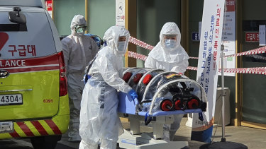 Medical workers wearing protective gear move a patient suspected of contracting the virus transfer him to hospital.