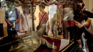 Visitors look at a statue of a turtle at the Ngoc Son Temple at Hoan Kiem lake in Hanoi, Vietnam, on Saturday.