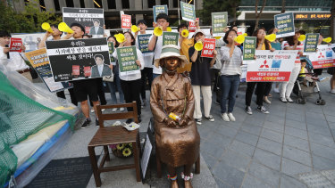 "Students denounce Japan's exports control on South Korea, near a statue of a girl symbolising wartime ""comfort women"" in front of the Japanese embassy in Seoul."