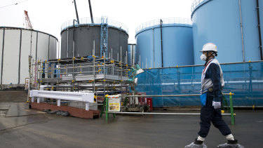 An employee walks past storage tanks for contaminated water at the tsunami-crippled Fukushima Dai-ichi nuclear power plant.
