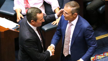 Premier Mark McGowan and Health Minister Roger Cook celebrate on the floor of WA's Legislative Assembly after the passage of the government's euthanasia legislation.