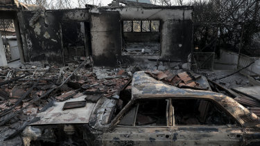 A burnt automobile stands in front of a destroyed house in Mati .