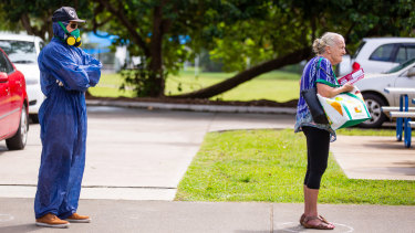 A voter wearing a protective suit and a gas mask stands spaced apart behind another voter outside a polling station during the local government elections in Noosa.