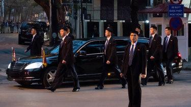 Bodyguard walk alongside a limousine carrying Kim as he arrives in Vietnam in February.