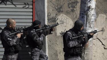 Gang related violence: elite police patrol one day after coming under fire during a shift change in the Alemao slum complex in Rio de Janeiro, Brazil.