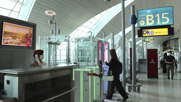 A woman enters the face and iris-recognition gate to board a plane at Dubai Airport, in the United Arab Emirates.