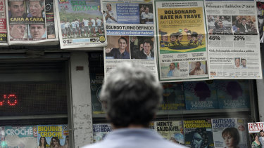 A man reads the headlines announcing the results of the Brazilian presidential election, in Rio de Janeiro.
