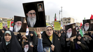 Demonstrators in Tehran hold up portraits of Supreme Leader Ayatollah Ali Khamenei during a pro-government rally denouncing last week's violent protests over a fuel price hike.