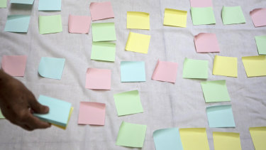 A protester places blank Post-it notes on a sheet during a lunchtime protest in a Hong Kong shopping mall.