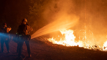 Firefighters douses flames with water during a firing operation to contain the Bear fire in Oroville, California.