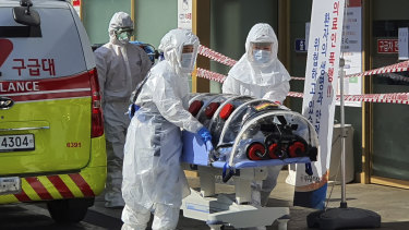 Medical workers move a patient suspected of having coronavirus from an ambulance to a hospital in Daegu, South Korea.