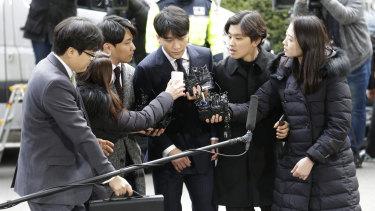 Seungri, centre, a member of a popular K-pop boy band Big Bang, arrives at the Seoul Metropolitan Police Agency on Thursday.