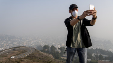 A tourist from San Diego takes a selfie as smoke from the Camp Fire fills the air in San Francisco, California,  on Friday.
