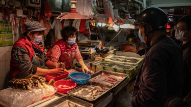 Residents wearing face masks buy seafood at a wet market in China.
