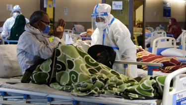 A health workers in personal protective equipment assists a patient at a makeshift COVID quarantine facility set up in a banquet hall in Delhi, India,