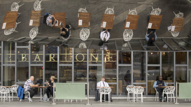 Customers sit at tables outside a pub at the Grand Central shopping center in Birmingham, UK.