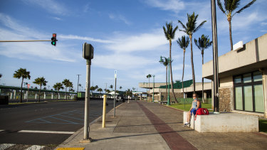 A traveller sits outside Kahului Airport in Hawaii. Tourism makes up one-fifth of Hawaii's economy gross domestic product, with 10 million visitors last year - that's all but vanished now.