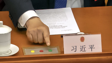 Chinese President Xi Jinping reaches to vote on an earlier piece of national security legislation concerning Hong Kong.