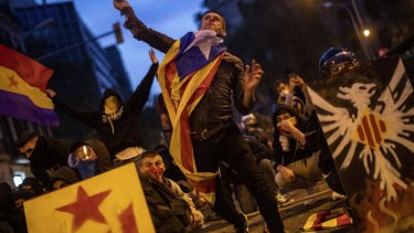 A Catalan pro-independence protester throws a stone during clashes with police in Barcelona, Spain.